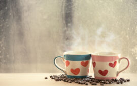 two lovely glass with coffee bean on rainy day window background  in vintage color tone