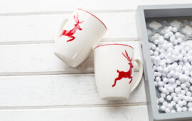 Two white coffee cups with a Christmas deer pattern. Beautiful holiday glass cups